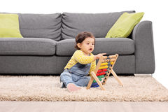 Bambina che gioca con un abaco messo sul pavimento Immagine Stock Libera da Diritti