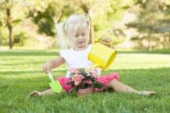 Bambina che gioca giardiniere con i suoi strumenti e vaso di fiore Fotografia Stock