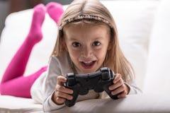 Bambina che gioca i videogiochi a casa Fotografia Stock Libera da Diritti