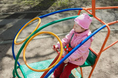 Bambina che gioca l'elicottero interno della barra di scimmia sul campo da giuoco all'aperto immagine stock