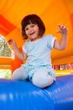 Bambina che gioca nel castello di rimbalzo gonfiabile immagine stock libera da diritti