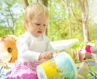 Bambina che gioca nel parco con un secchio ed i pastelli Fotografie Stock