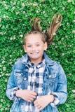 Bambina che gioca nel parco nel fondo verde con i fiori fotografia stock