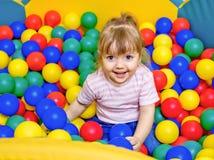 Bambina che gioca nelle palle di stagno Immagine Stock