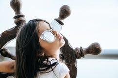 Bambina che gioca per essere un marinaio su un balcone con un timone della barca fotografia stock