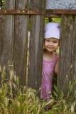 Bambina che gioca sbirciata un fischio con una lacuna in una plancia rotta Fotografia Stock Libera da Diritti