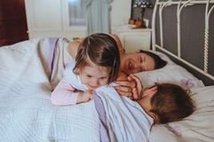 Bambina che gioca sopra il ragazzo che si trova nel letto Immagine Stock Libera da Diritti