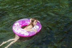 Bambina che gioca su un tubo gonfiabile un giorno di estate Fotografia Stock