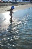 Bambina che gioca sulla spiaggia al tramonto fotografie stock libere da diritti