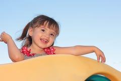 Bambina che gioca sulla strumentazione del campo da giuoco Fotografia Stock Libera da Diritti