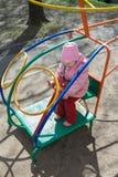 Bambina che gioca trattando l'elicottero della barra di scimmia del gioco sul campo da giuoco all'aperto fotografia stock
