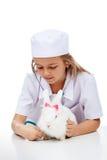 Bambina che gioca veterinario con il suo coniglio Immagini Stock Libere da Diritti