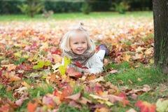 Bambina che gode dell'autunno nel parco immagini stock