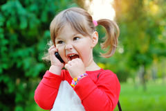 Bambina che grida nel telefono in un parco Immagini Stock