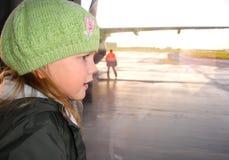 Bambina che guarda attraverso la finestra dell'aeroporto Fotografie Stock