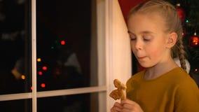 Bambina che guarda attraverso la finestra che mangia biscotto, genitori aspettanti per la vigilia di natale stock footage