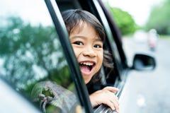 Bambina che guarda fuori alle finestre aperte con il sorriso immagini stock