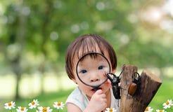 Bambina che guarda lo scarabeo di rinoceronte in giardino Immagini Stock Libere da Diritti