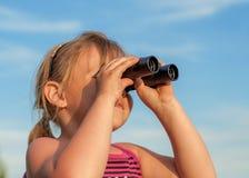 Bambina che guarda tramite il binocolo Immagine Stock
