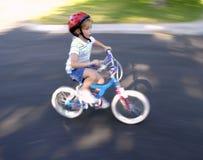 Bambina che guida una bici Fotografia Stock