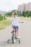 Bambina che guida una bicicletta Immagine Stock