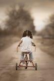 Bambina che guida via sul suo triciclo Fotografia Stock