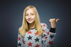 Bambina che indica dal dito al lato e che sorride alla macchina fotografica su Gray Fotografie Stock Libere da Diritti