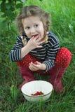 Bambina che indossa i gumboots rossi che prendono i lamponi maturi dalla ciotola bianca alla sua bocca Immagine Stock