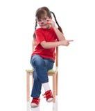 Bambina che indossa maglietta rossa e vetro che indicano da qualche parte Fotografie Stock Libere da Diritti