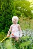 Bambina che innaffia l'erba Fotografie Stock Libere da Diritti