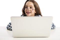 Bambina che lavora con un computer portatile Immagini Stock