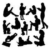 Bambina che legge le siluette di un libro Immagine Stock
