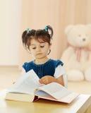 Bambina che legge un libro alla tavola Fotografia Stock Libera da Diritti