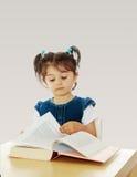 Bambina che legge un libro alla tavola Fotografia Stock