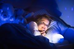 Bambina che legge un libro a letto Immagine Stock