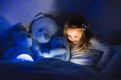 Bambina che legge un libro a letto Fotografia Stock Libera da Diritti