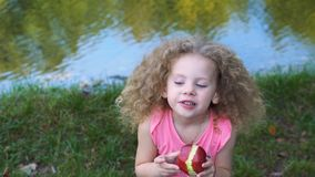 Bambina che mangia Apple all'aperto video d archivio