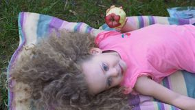 Bambina che mangia Apple all'aperto stock footage