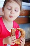 Bambina che mangia bagel turco fotografia stock