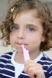 Bambina che mangia caramella dolce con il fronte sporco Fotografia Stock