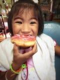 Bambina che mangia ciambella Fotografia Stock