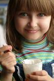 Bambina che mangia crema Fotografia Stock