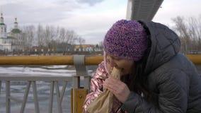 Bambina che mangia hot dog e che alimenta camminata motherwhile sulla via della città archivi video