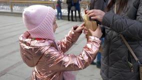 Bambina che mangia hot dog saporito in città nell'inverno stock footage
