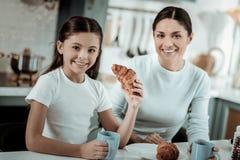 Bambina che mangia i croissant nella cucina immagine stock
