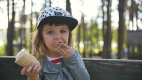 Bambina che mangia il gelato sul banco stock footage