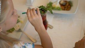 Bambina che mangia insalata e che beve la bevanda della bacca nel caffè stock footage