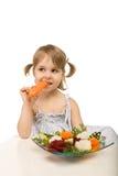 Bambina che mangia le verdure - chomping una carota Fotografia Stock