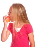 Bambina che mangia mela rossa su bianco immagine stock libera da diritti