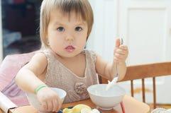 Bambina che mangia nel fare da baby-sitter, bambino che mangia panna acida immagine stock libera da diritti
